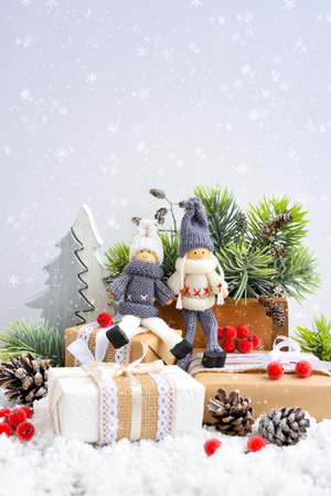 Christmas composition with toys dolls and spruce branches and festive decorations on snow. Christmas or New Year greeting card.