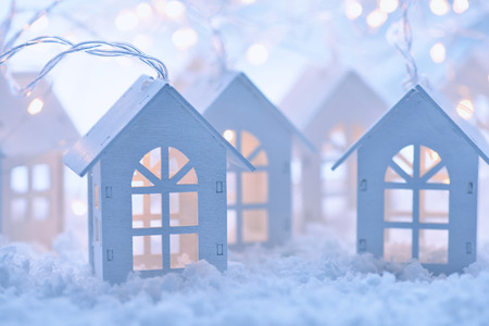 Christmas and New Year background with a garland in the form of little houses on the snow Stock Photo