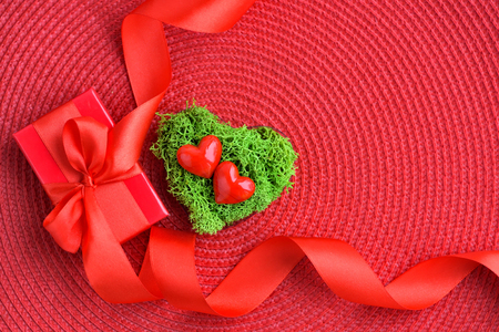 Valentines Day background. Hearts in green moss with red gift box. Top view Stock Photo