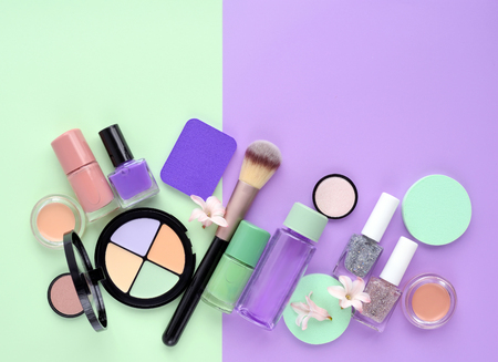Decorative cosmetics and nail polishes on color background, with empty space for text. Top view