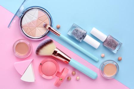 Make-up borstel en decoratieve cosmetica op kleur achtergrond. Minimale stijl. Bovenaanzicht Stockfoto