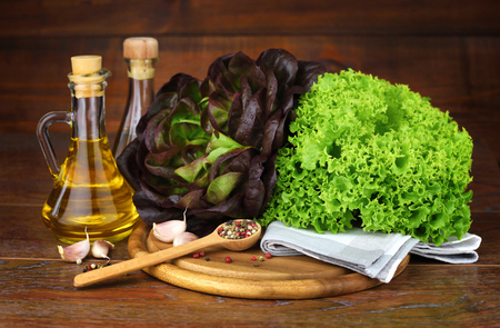 Fresh green and red lettuce, oil, seasonings on the wooden background