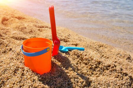 Bright plastic сhildren's beach toys - bucket and shovels on sand near sea