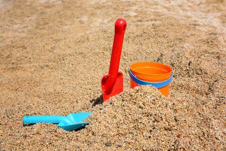 Bright plastic сhildren's beach toys - bucket and shovels on sand near sea