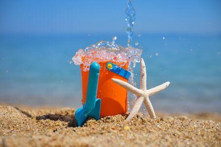 Giocattoli da spiaggia di plastica brillante Ñ per bambini e una stella marina sulla sabbia vicino al mare. Concetto di vacanza estiva