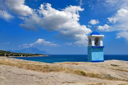 Small chapel on beautiful rocky coast near sea. Mount Athos on horizon. Sithonia, Halkidiki, Greece. Stock Photo
