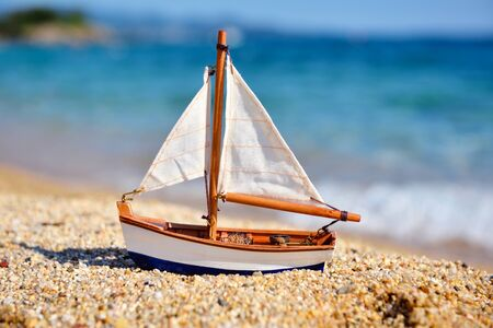 Miniature toy sailboat on the beach against the background of the sea and waves. Vacation and travel concept. Stok Fotoğraf - 130025270