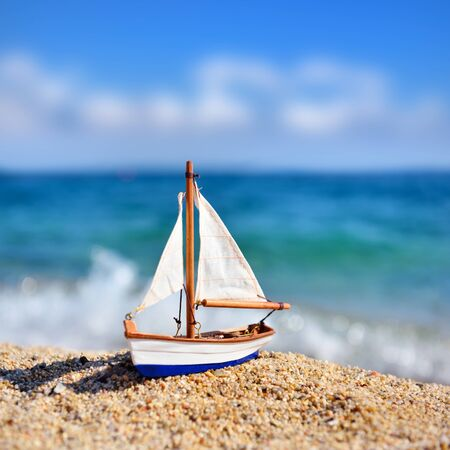 Miniature toy sailboat on the beach against the background of the sea and the blue sky. Vacation and travel concept. Stok Fotoğraf - 130025178