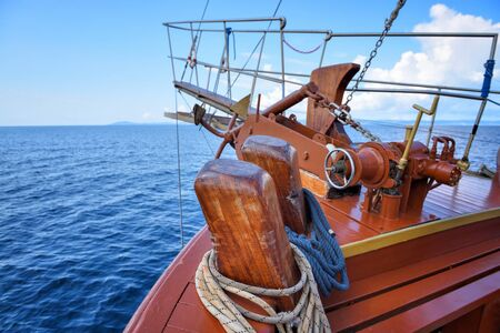 A anchor, ropes and bow of a wooden sailing yacht against the background of the sea and the blue sky Stok Fotoğraf - 130024619