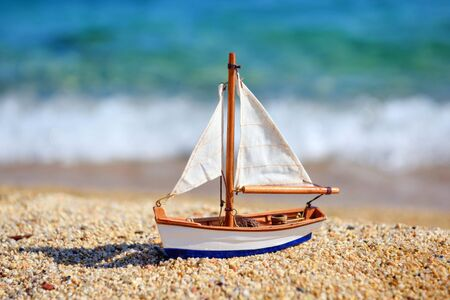 Miniature toy sailboat on the beach against the background of the sea and waves. Vacation and travel concept. Stok Fotoğraf - 130020610