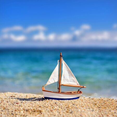 Miniature toy sailboat on the beach against the background of the sea and the blue sky. Vacation and travel concept. Stok Fotoğraf