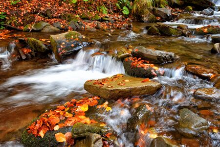 Beautiful landscape with a waterfall in the autumn forest Reklamní fotografie