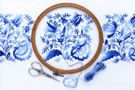 Embroidery hoop with fabric, sewing needle and thread, top view. Blue floral ornament on a white background