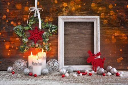 Christmas composition with candles, photo frame and festive decorations on a wooden background. Christmas or New Year greeting card.