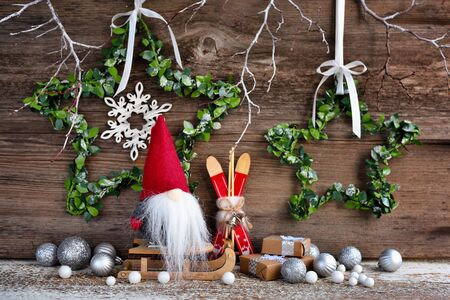 Christmas composition with a gnome on sleigh and festive decorations on a wooden background. Christmas or New Year greeting card.