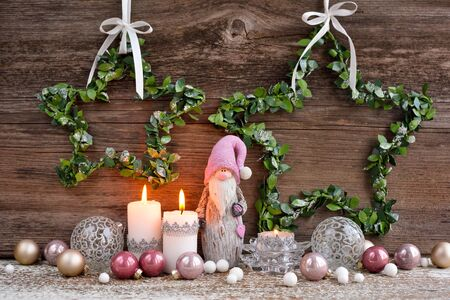 Christmas composition with candles, gnome figurine and festive decorations on a wooden background. Christmas or New Year greeting card.