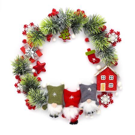 Weihnachts- oder Neujahrskomposition. Runder Rahmen aus Weihnachtsschmuck und Fichtenzweigen auf weißem Hintergrund. Urlaubs- und Feierkonzept für Postkarte oder Einladung. Ansicht von oben Standard-Bild