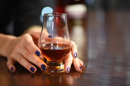 Woman hand holds a glass of whisky. Seasonal holidays concept