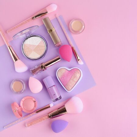 Makeup brushes and decorative cosmetics on pastel color background, with empty space for text. Top view