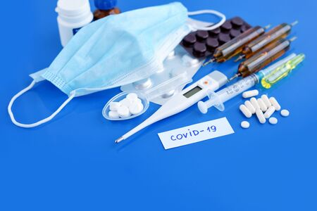 Medical protective mask with pills, thermometer, medicines, syringes on blue desk. Dangerous virus COVID-19. Healthcare and medical concept.