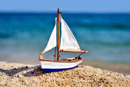 Miniature toy sailboat on the beach against the background of the sea and waves. Vacation and travel concept.