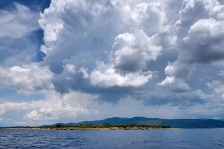 View of the shore from the sea. Landscape with the sea and beautiful clouds in the blue sky. Sithonia, Halkidiki, Greece.