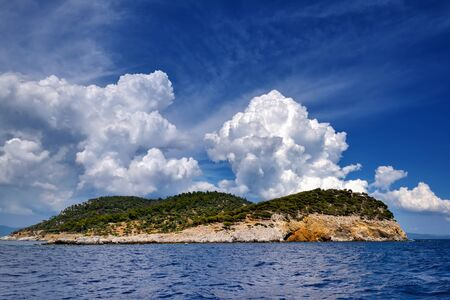 Landscape with the sea, island and beautiful clouds in the blue sky. Kelifos island, Aegean Sea, Halkidiki, Greece, view from the sea.