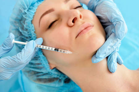 The doctor cosmetologist makes the rejuvenating facial injections procedure for tightening skin. Cosmetology concept.