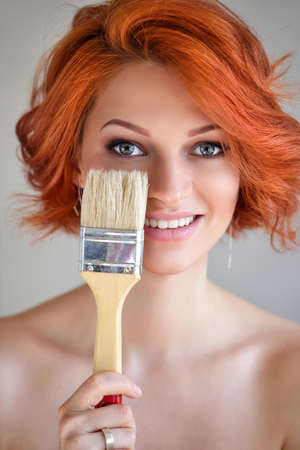 Portrait of young beautiful redhaired woman with paintbrush as if ironically putting on make-up