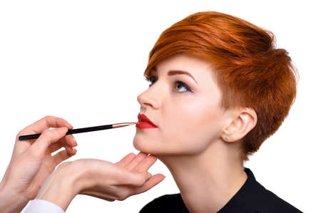 Makeup artist applies lipstick brush on the lips of the model. Beautiful young woman with short red hair. Makeup detail.