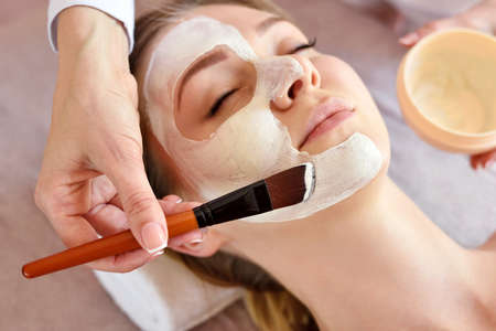 Face peeling mask, spa beauty treatment, skincare. Woman getting facial care by beautician at spa salon, side view, close-up Zdjęcie Seryjne