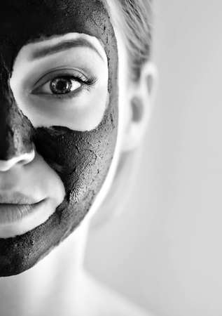 Beautiful girl with mask from clay on his face. Cosmetic mask. Beauty face. Beauty wellness concept. Black & white photo Zdjęcie Seryjne
