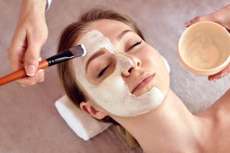 Face peeling mask, spa beauty treatment, skincare. Woman getting facial care by beautician at spa salon, close-up Zdjęcie Seryjne