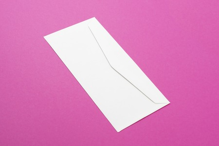 Top view of white blank envelope on pink background. Minimal concept. Fashionable color.