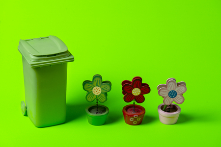 Green trash can with flowers on a green background. 免版税图像