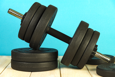 Big dumbbell on a colored background. Sports equipment and inventory. 版權商用圖片