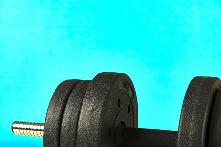 Big dumbbell on a colored background.Sports equipment, protein.