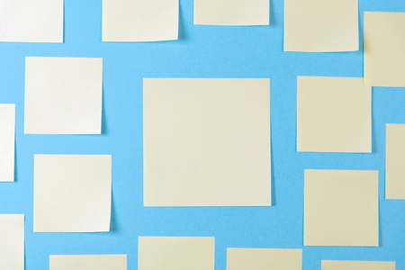 Blank yellow sticky notes on a blue background, concept of business work. Yellow memo stickers on blue wall. Mock-up.