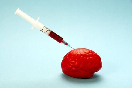 Red brain on a blue background with a nootropic syringe. Injection into the brain. Stock Photo