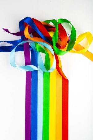 LGBT flag symbol made of satin ribbons on a white background. A rainbow of ribbons mixes with each other. Variety of sexuality.