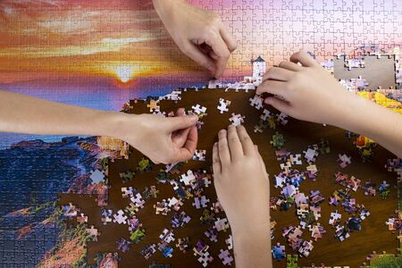 children and adult hands stack color puzzle on wooden table