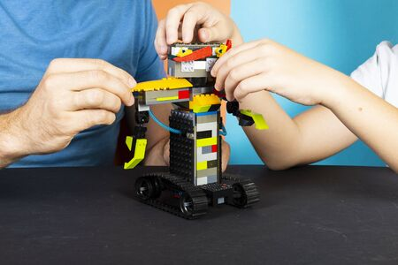 A man and a boy assemble from a constructor of a robot. Stockfoto