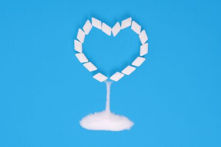 Sugar cubes on a blue background in the shape of a heart with sprinkling sugar. Diabetes, heart disease Stockfoto