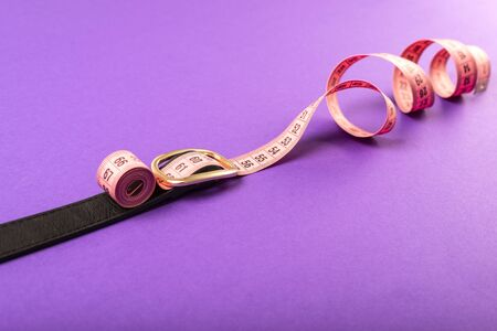 pink spiral measuring tape on a black waist belt on a violet background, the concept of excess weight and weight loss