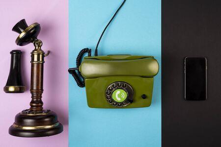 Viejo teléfono vintage marrón junto con un teléfono verde con cable y un teléfono móvil en varios fondos de color. El concepto de desarrollo de las comunicaciones telefónicas.