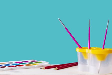 School set of pencils, paints, glass brush, on a blue background with space for text. back to school. office supplies, stationery. Drawing set.