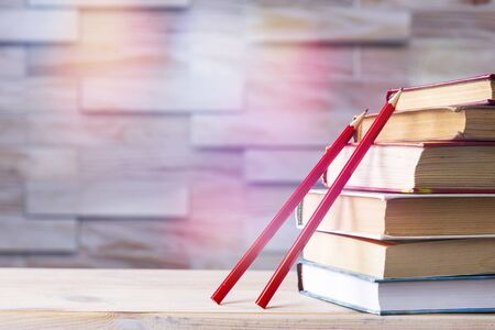 stack of books and two red wooden pencils on wooden background, back to school concept.