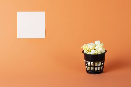 The basket is filled with crumpled paper on an orange background and a yellow sticker for notes Stok Fotoğraf