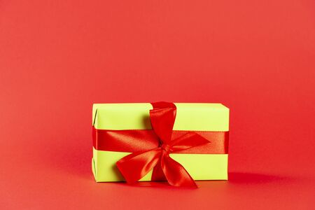 Christmas composition. Green gift box with a red ribbon on a red background. Side view. a Christmas gift.