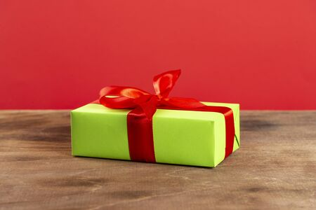 Christmas composition. Green gift box with red ribbon on a wooden table and red background. Side view. a Christmas gift.
